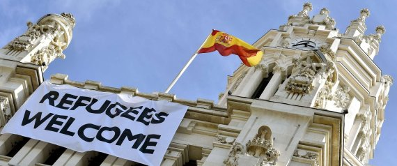 "A Spanish flag flies above a banner reading ""Refugees Welcome"" hanging on the facade of the Cibeles Palace, the Madrid City Hall, on September 7, 2015. The numbers of migrants have spiked since September 4, 2015, when Austria and Germany threw open their borders and eased travel restrictions to allow in thousands who had made it to Hungary, which has balked at the influx. AFP PHOTO/ GERARD JULIEN"